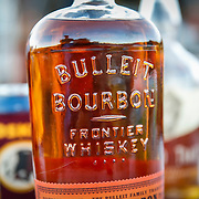 SHOT 10/16/16 6:21:37 PM - Bulleit bourbon at the ready while camping along the White Rim Trail. The White Rim is a mountain biking trip in Canyonlands National Park just outside of Moab, Utah. The White Rim Road is a 71.2-mile-long unpaved four-wheel drive road that traverses the top of the White Rim Sandstone formation below the Island in the Sky mesa of Canyonlands National Park in southern Utah in the United States. The road was constructed in the 1950s by the Atomic Energy Commission to provide access for individual prospectors intent on mining uranium deposits for use in nuclear weapons production during the Cold War. Four-wheel drive vehicles and mountain bikes are the most common modes of transport though horseback riding and hiking are also permitted.<br /> (Photo by Marc Piscotty / &copy; 2016)
