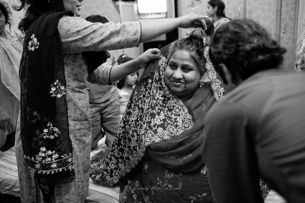Family and friends put on a beautiful scarf on Loebna during a traditional hindu ceremony called godh bharai. 6 months pregnant from her 3rd child, the celebration is to bless the pregnant woman with gifts, fruits and sweets for the impending arrival of new life. The ceremony may include adorning the woman with a beautiful scarf, making her wear flowered bangles, filling her lap with fruit and gifts and have her eat sweets. Lahore, Pakistan 2010