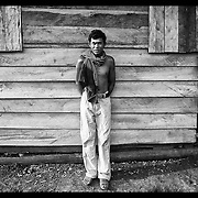 A former Khmer Rouge soldier pauses outside his rough wooden shack in Pailin, Cambodia,  to be photographed as his children look.  Pailin, near the Thai-Cambodian border was once one of many Khmer Rough strongholds where timber and mining profits were funneled into the Khmer Rouge operation.