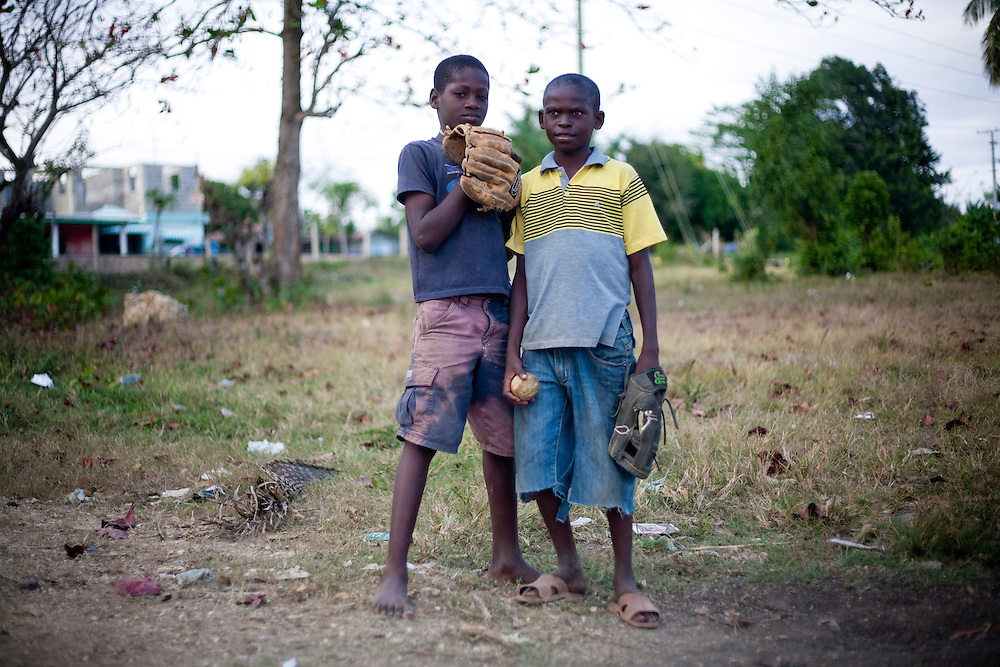 Joe Malte, left, and Jose Hermando, both age 11, pose for a photo while playing baseball in an open field on Friday, February 26, 2010 in San Antonio de Guerra, Dominican Republic.