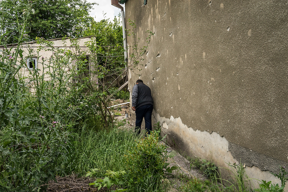 A man shows a shrapnel-damaged building from recent fighting on Monday, May 9, 2016 in Martakert, Nagorno-Karabakh.