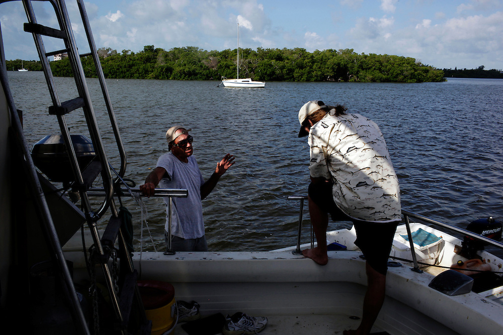 Randy Eibler, right, also known as Last Chance Randy, talks to Hillbilly Jim, left, who also lives on a boat anchored in Estero Bay, Fla. More than a dozen people call the bay near Fort Myers beach home.
