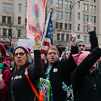 Protestors march past the Trump International Hotel booing and showing a middle finger in the Women's March on Washington D.C., January 21, 2017