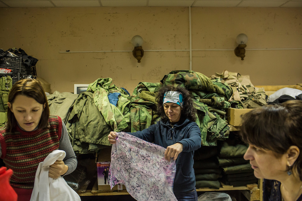 DNIPROPETROVSK, UKRAINE - NOVEMBER 16, 2014:  Yana Sobolenko, 39, an engineer, left, Lyudmyla Makaida, 48, a designer, center, and Tanya Volynets, 46, a lawyer, right, look at fabric they will use to cut fabric to make underwear for soldiers at the Dnipropetrovsk Volunteer Logistics Center, a charity organization that produces supplies for pro-Ukrainian fighters battling rebels in the country's East, in Dnipropetrovsk, Ukraine. CREDIT: Brendan Hoffman for The New York Times