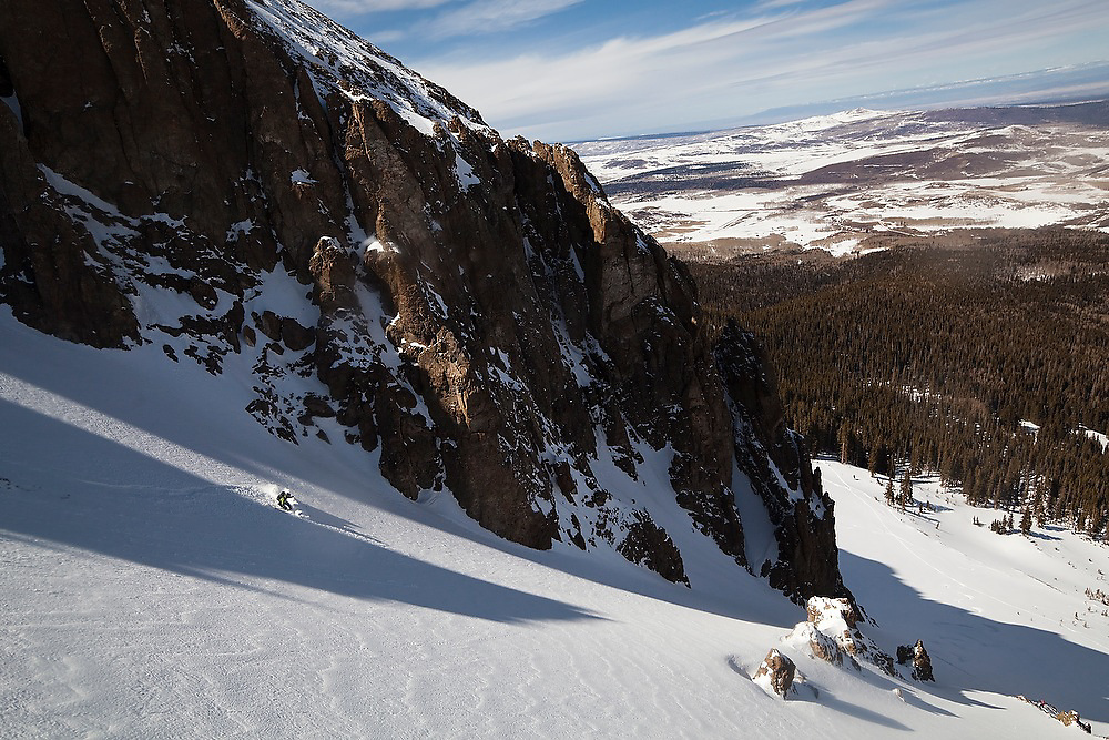 Backcountry skier Judd MacRae drops into a steep couloir below the summit of Hayden Peak, San Juan Mountains, Colorado.