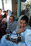 The women and men are separated during the wedding celebrations which involve eating, dancing and listening to music. Dancing and music were forbidden during the rule of the Taliban.More than one hundred women gathered to take part the wedding ceremony for  Afghan bride Mushgar in the neighborhood of Golbahar outside of Kabul Afghanistan April 17,2004.Marriges in Afghanistan are commonly arranged between families and not by the yound people themselves. In arranging a marriage families take several factors into account:sectarian membership,ethnic group,family status, kin relationship, economic benifits, and (in obtaining  a bride) industriousness and ability to cooperate with the groom's female realations.Women were, after marriage, viewed as the husband's family's prperty to the extent that if her husband died she was forced to marry his brother or next to kin.Tribal laws viewed marriages as alliances between groups:women were pawned into marriages, not allowed to divorce, total obedience to the husband and his family was expected nad they were prevented from getting any education.(Photo by Heidi Levine/Sipa Press).