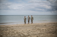 US Army soldiers pay respect to the silence played by a trumpetis on Utah beach