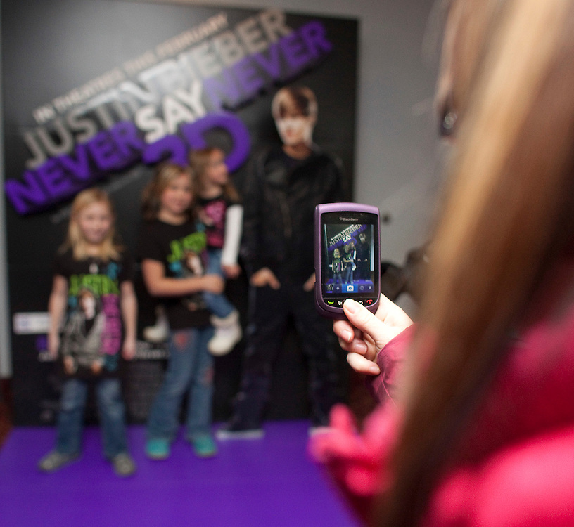 Stratford, Ontario ---11-02-10---  Alyssa Copeland ,left, an d Justin Bieber's cousins Kiersten Mackay and Lillee Reith pose for photos in front of a movie poster at the Stratford Cinema during the debut of Justin's new movie &quot;Never Say Never&quot; in his hometown of Stratford, Ontario, February 10, 2011.<br /> GEOFF ROBINS The Globe and Mail