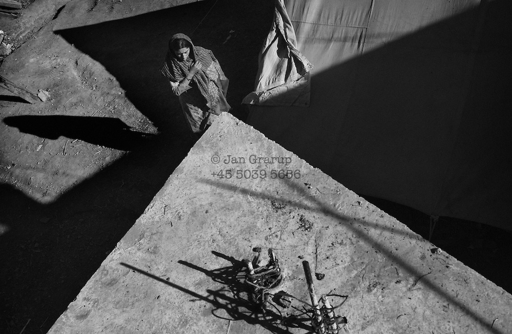 A woman in front of her tent in the village of Lamnia, on a remote mountainside. The isolated villagers here were among the last to receive emergency relief. Many weeks after the earthquake, rescue teams were finding distant villages that had not yet received help, and where survivors had died of their injuries.<br /> Lamnia -  Dec. 2005