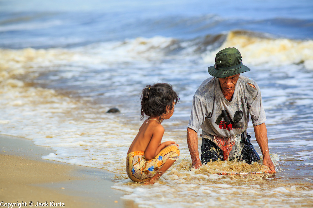 04 NOVEMBER 2012 - KAO SENG, SONGKHLA, THAILAND:  A man and his child look for snails and clams in the surf in Kao Seng. Kao Seng is a traditional Muslim fishing village on the Gulf of Siam near the town of Songkhla, in the province of Songkhla. In general, their boats go about 4AM and come back in about 9AM. Sometimes the small boats are kept in port because of heavy seas or bad storms.    PHOTO BY JACK KURTZ