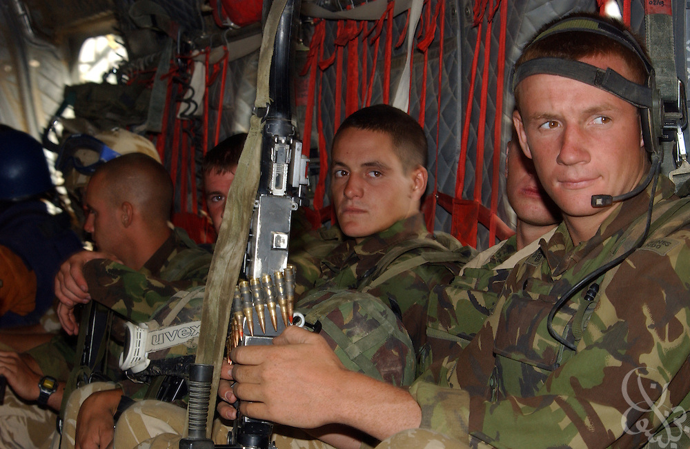 "British Royal Marines of 45 Commando ride inside a Chinook helicopter during an ""eagle vehicle check point"" (VCP) mission as part of the ongoing Operation Buzzard July 8, 2002 in southeastern Afghanistan. During VCPs, small groups of marines are dropped quickly by helicopters to search random vehicles on dirt roads and trails near the Pakistan-Afghanistan border to deny al Qaeda and Taliban fighters freedom of movement across the region."