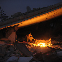 A palestinian man from the Palestinian Hammuda family sits around the fire as he spends the night amid the rubble of his destroyed house in Jabalia's Ezbet Abed Rabbo district in the northern Gaza Strip on January 26, 2009. An ongoing Saudi campaign to raise aid for the battered Gaza Strip has so far raised 59.8 million dollars, including 10.7 million dollar from King Abdullah bin Abdul Aziz and his crown prince.