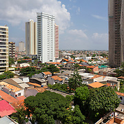 Brazil, emerging country, 2011: emergence of middle class stimulates construction of apartment buildings which replace individual houses in Belem, Para State. Building at right is still in construction, covered with protective safety screen debris netting.