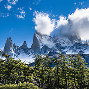 """Mount Fitz Roy (3405 meters or 11,170 feet) rises abruptly above native forest in the southern Andes mountains, near El Chaltén village, in Los Glaciares National Park, Argentina, South America. In 1877, explorer Perito Moreno named """"Cerro Fitz Roy"""" for Robert FitzRoy (no space before the capital R) who, as captain of the HMS Beagle, had travelled up the Santa Cruz River in 1834 and charted much of the Patagonian coast. First climbed in 1952 by French alpinists Lionel Terray and Guido Magnone, Mount Fitz Roy has very fickle weather and is one of the world's most challenging technical ascents. It is also called Cerro Chaltén, Cerro Fitz Roy, and Monte Fitz Roy (with a space before the R). Chaltén comes from a Tehuelche (Aonikenk) word meaning """"smoking mountain"""" (explained by frequent orographic clouds). Cerro is a Spanish word meaning hill. El Chaltén village was built in 1985 by Argentina to help secure the disputed border with Chile, and now tourism supports it, 220 km north of the larger town of El Calafate. The foot of South America is known as Patagonia, a name derived from coastal giants, Patagão or Patagoni, who were reported by Magellan's 1520s voyage circumnavigating the world and were actually Tehuelche native people who averaged 25 cm (or 10 inches) taller than the Spaniards. Mount Fitz Roy is the basis for the Patagonia company's clothing logo, after Yvon Chouinard's ascent and subsequent film in 1968. Panorama stitched from 2 overlapping photos."""