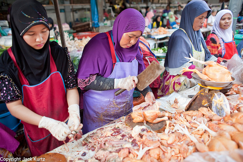 """Sept 25, 2009 -- PATTANI, THAILAND: Muslim women butcher chickens for customers in the morning market in Pattani, Thailand. Thailand's three southern most provinces; Yala, Pattani and Narathiwat are often called """"restive"""" and a decades long Muslim insurgency has gained traction recently. Nearly 4,000 people have been killed since 2004. The three southern provinces are under emergency control and there are more than 60,000 Thai military, police and paramilitary militia forces trying to keep the peace battling insurgents who favor car bombs and assassination.  Photo by Jack Kurtz"""
