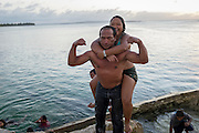 """A """"muscleman"""" flexes after carrying a girl up from the water onto Sugar Dock during the lively hour. The beach and dock is a popular local swimming and party spot on the island."""