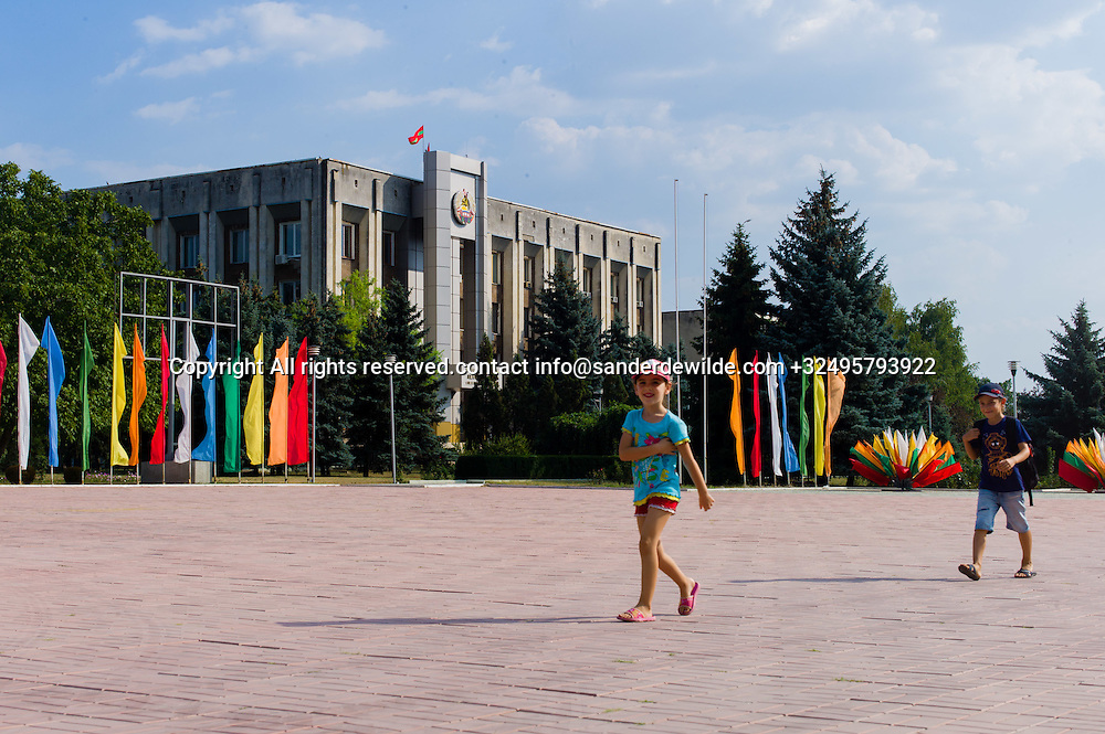 20150829  Moldova, Transnistria,Pridnestrovian Moldavian Republic (PMR) Dubushari.Kids passing by City hall building decorated with flags in all colors, prepared for the 25th indepence day on the 2nd of September.