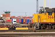 A Union Pacific locomotive sits idle as trucks deliver international container cargo to the Global II intermodal terminal in North Lake, IL. The Global II terminal is one of the busiest container terminals in the country, unloading containers from inbound trains and delivering the goods to customers in the Chicago area.