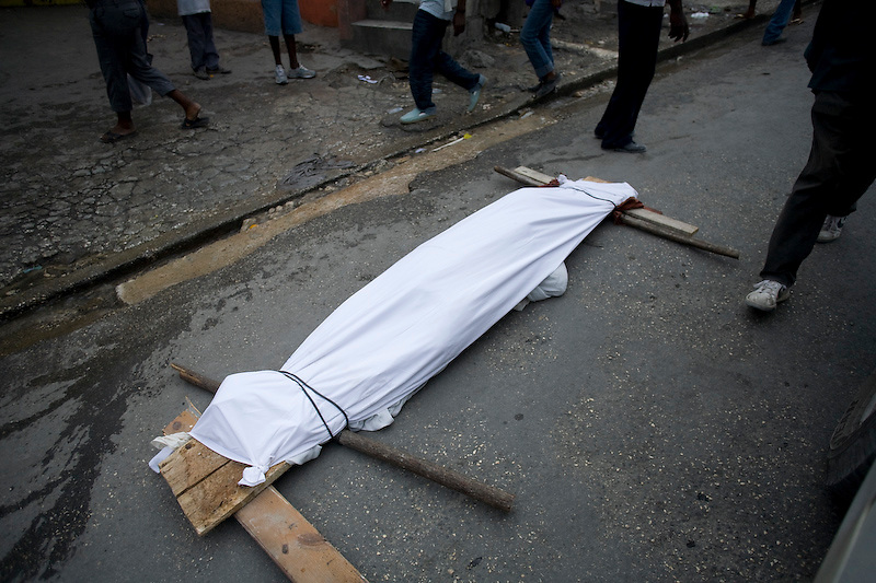 A body being carried to a mass grave in Tabarre, Haiti. Photo by Ben Depp 1/14/2010