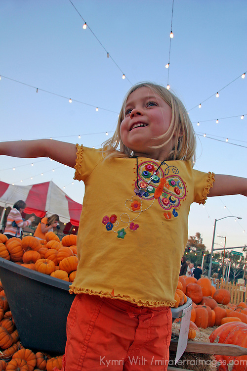 USA, California, Encinitas.  A young girl enjoys a local pumpkin patch carnival.