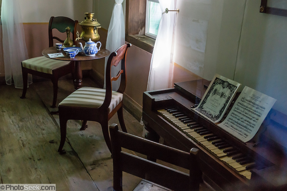 """At Fort Ross, the piano forte and exhibit furnishings in Rotchev House exactly copy the early 1800s originals and are set up to portray the late 1830s. Built circa 1836, Rotchev House is the only original remaining structure from Russia's thriving settlement in California. Fort Ross State Historic Park, which preserves a former Russian colony (1812-1842) on the west coast of North America, in what is now Sonoma County, California, USA. Visit Fort Ross and dramatic coastal scenery 11 miles north of Jenner on California Highway One.  Initially, sea otter pelts funded Russian expansion, but by 1820, overhunting motivated the Russian-American Company to introduce moratoriums on hunting seals and otters, the first marine-mammal conservation laws in the Pacific. Russian voyages greatly expanded California's scientific knowledge. For centuries before Europeans arrived, this site was called Metini and had been occupied by the Kashaya band of Pomo people who wove intricate baskets and harvested sea life, plants, acorns, deer, and small mammals. Sponsored by the Russian Empire, """"Settlement Ross"""" was multicultural, built mostly by Alaskan Alutiiq natives and occupied mostly by native Siberians, Alaskans, Hawaiians, Californians, and mixed Europeans. Renamed """"Ross"""" in 1812 in honor of Imperial Russian (Rossiia), Fortress Ross was intended to grow wheat and other crops to feed Russians living in Alaska, but after 30 years was found to be unsustainable. Fort Ross was sold to John Sutter in 1841, and his trusted assistant John Bidwell transported its hardware and animals to Sutter's Fort in the Sacramento Valley. Fort Ross is a landmark in European imperialism, which brought Spanish expanding west across the Atlantic Ocean and Russians spreading east across Siberia and the Pacific Ocean. In the early 1800s, Russians coming from the north met Spanish coming from the south along the Pacific Coast of California, followed by the USA arriving from the east in 1846 for the Mexican-Ameri"""