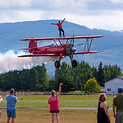 A veteran wingwalking student does a low pass on a Stearman 450 biplane piloted by expert pilot and wingwalker Mike Mason, over Sequim WA airport. This during the Air Affaire airshow event. Mike and wife Marilyn teach students from all over the world to wing walk. http://www.masonwingwalking.com/