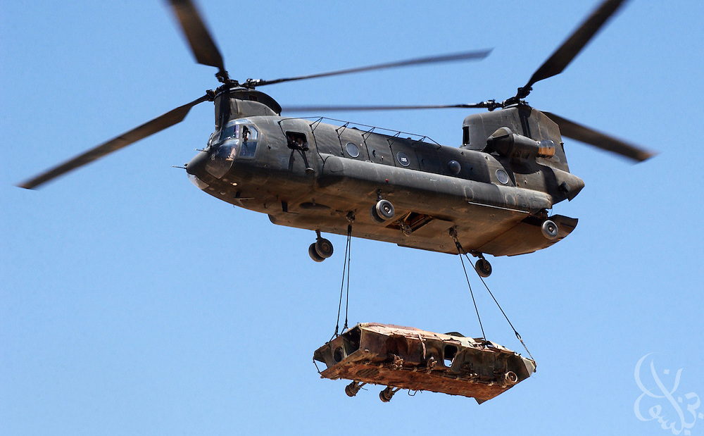 A U.S. Army CH-47 Chinook helicopter lifts the wrecked frame of a Soviet armored personnel carrier (APC)  as it participates in a mission to clear debris June 20, 2002 from the Bagram air base in Afghanistan.  Bagram, a former Soviet military base is littered with hundreds of wrecked vehicles and airplanes along with thousands of unexploded ordinance left over from the Soviet occupation of Afghanistan.