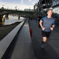 UK. London. A runner runs in front of London's Bankside developments between Southwark Bridge and The Tate Modern..