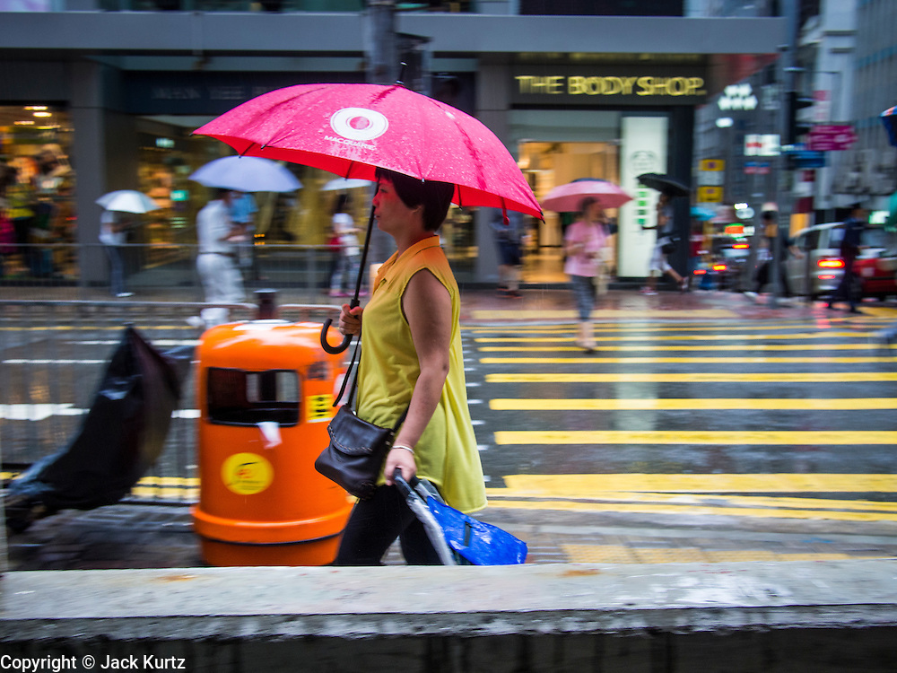 13 AUGUST 2013 - HONG KONG:  A woman walks up Queen's Road in Hong Kong while rain from Typhoon Utor hits the island. Typhoon Utor (known in the Philippines as Typhoon Labuyo) is an active tropical cyclone located over the South China Sea. The eleventh named storm and second typhoon of the 2013 typhoon season, Utor formed from a tropical depression on August 8. The depression was upgraded to Tropical Storm Utor the following day, and to typhoon intensity just a few hours afterwards. The Philippines, which bore the brunt of the storm, reported 1 dead in a mudslide and 23 fishermen missing at sea. The storm brushed by Hong Kong bringing several millimeters of rain and moderate winds to the island but causing no reported damage or injuries. It is expected to make landfall in China.  PHOTO BY JACK KURTZ