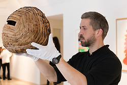 Christies, St James, London, March 4th 2016. A gallery technician displays Andy Goldsworthy's leafwork &quot;Sweet Chestnut Leaves and Blackthorns&quot; created in Dumfriesshire in 2013, at the preview for the It&rsquo;s Our World charity auction at Christie's. Over 40 leading artists including David Hockney, Sir Antony Gormley, David Nash, Sir Peter Blake, Yinka Shonibare, Sir Quentin Blake, Emily Young and Maggi Hambling have committed artworks to the It&rsquo;s Our World Auction in support of The Big Draw and Jupiter Artland Foundation, to be sold at Christie&rsquo;s London on 10 March 2016.<br />  ///FOR LICENCING CONTACT: paul@pauldaveycreative.co.uk TEL:+44 (0) 7966 016 296 or +44 (0) 20 8969 6875. &copy;2015 Paul R Davey. All rights reserved.