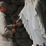 A reverent dedication attendee places a rose at the foot of the statue of Mary.<br />