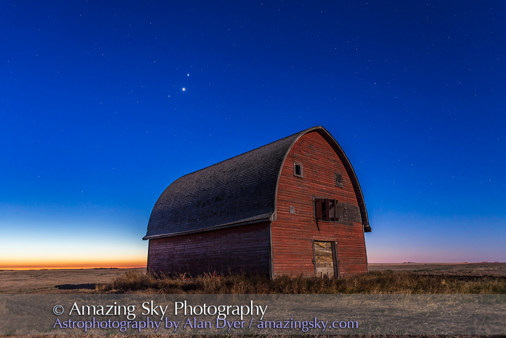 Mars, Venus and Jupiter (in that order from top to bottom) in a triangle, in conjunction, over an old red barn near Vulcan, Alberta, in the morning twilight, October 28, 2015. Illumination is from the nearly Full Hunter&rsquo;s Moon in the west. The trio of planets were in Leo in a fine conjunction not to be repeated until November 21, 2111. <br /> <br /> This is a stack of 6 exposures for the ground, mean combined to smooth noise, and one exposure for the sky, all  10 seconds at f/4 and ISO 800 with the Canon 6D and Canon 24mm lens.