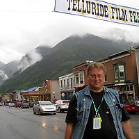 Tom Goodman, Telluride Film Festival Conversations Manager on Colorado Avenue with film festival banner, 2008.