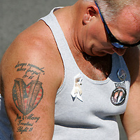 A family member of a victim in the World Trade Center attack slumps over at the site of the disaster on the fourth anniversary of the attack in New York September 11, 2005. The man's tattoo is in the memory of victims Mary and James Trentini killed in the crash of American Airlines flight 11. The Trentini's were scheduled to fly out Sept. 10 but Mr. Trentini was summoned for a day of jury duty on the 10th so they rebooked for Sept. 11.