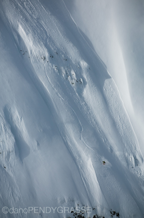 Professional snowboarder Mads Jonsson negotiates his way down a steep mountain face outside of Terrace, BC, Canada.