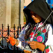 Woman in traditional garb embroidering on the island of Amantani in Lake Titicaca, Peru.