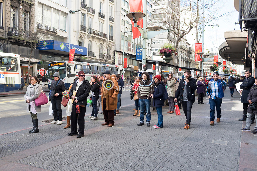 Montevideu, Uruguai, 2016. Avenida 18 de Julho (Avenida 18 de Julio),eh a avenida mais importante da cidade. Em 18 de Julho de 1830 foi promulgada a primeira Constituição do pais.  Comeca na Plaza Independencia, nos limites da Ciudad Vieja (Cidade Velha), atravessa os bairros Centro e Cordon e termina no Obelisco de Montevideu em Tres Cruces, onde se encontra com Artigas Boulevard.   Pessoas em uma parada de onibus. = Avenida 18 de Julio, or 18 de Julio Avenue, is the most important avenue in Montevideo, Uruguay. It is named after the date the first Constitution of Uruguay was written: July 18, 1830. people waiting at the bus stop.