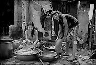 Young mother washes clothes while her friend prepares a bath for her baby in a tight alleyway just steps away from the shore of Manila Bay in Parola Slum in Manila's Tondo District.<br /> <br /> Most of the vast slums of Manila's Tondo District, like Parola, are not only just a meter or two above sea level but, in a seismically active area, are built on reclaimed land beside Manila Bay.  <br /> <br /> On Maplecroft's Climate Change Vulnerability Index, Manila ranks as the world's second most vulnerable city to climate change.  Manila's Tondo is Manila's district most vulnerable to climate change-induced sea rises, storm surges from increasingly strong typhoons and earthquake trigger tsunami.  It has a population density of nearly 78,000 people per square km (202,800 ppl/sq mi), according to a 2009 Cornell University report.  (Note: Manhattan has a population density of 26,939/km2 [69,771/sq mi].)