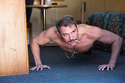 shirtless man with a mustache and cigarette in his mouth doing pushups in a rundown motel room