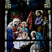 Stained glass image of Jesus lying in the manger with Mary, Joseph and choir of angels. (Sam Lucero photo)