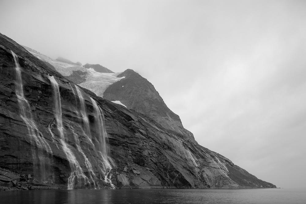 Greenland, Nuuk (Godthåb), Waterfall and receding alpine glacier in steep mountain cliffs along Nup Kangerdlua (Godthåb Fjord) on cloudy summer day