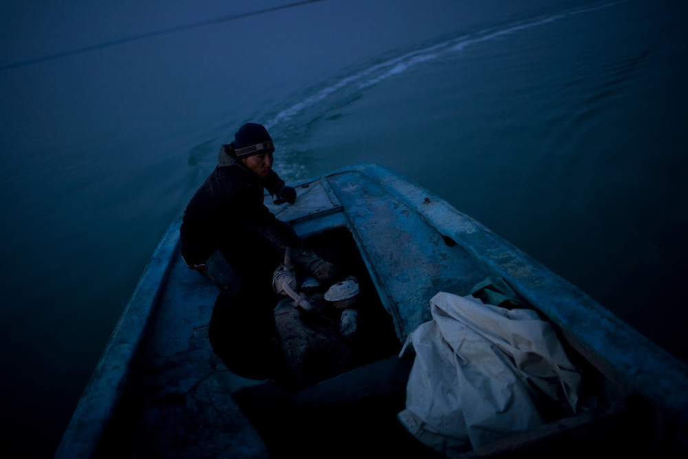 CREDIT: DOMINIC BRACCO II..SLUG:PRJ/KAZAKHSTAN..DATE:10/31/2009..CAPTION:Fisherman Almat Aidoraliev, 21 of Aralsk, steers his boat to check the status on another group of boaters while out on the Aral Sea on October 31, 2009...Aral Sea Overview: ..During the 1960s the USSR began irrigating the waters of the Aral Sea in southern Kazakhstan to combat their growing food crisis. The Soviets severely miscalculated and water began receding quickly from the port cities. The waters continued to recede. By 2000 the water was 80 km away from the city of Aralsk, a main seaport in Kazakhstan. In 2005 with help from the World Bank, construction began on a 13km dike that locals hoped would bring the waters back to their original shores. The project raised water quality and fishing was able to resume, however four years after completion of the dike the water is still 50km from Aralsk's port. Locals seem mixed on the possibility of the sea returning after more than 40 years without the sea. Fishermen from Aralsk make a three-hour path through soft desert road along the former seabed. The only source of income for many is cattle, horses, and camels, which have, began to overgraze the areas of the former seabed and surrounding desert. Because of this nutrient rich topsoil is lifted by the wind and the process of desertification continues.  .