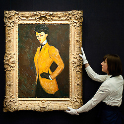 London, UK - 12 April 2013: A Sotheby's employee poses in front of Amedeo Modigliani  'L'Amazone' (Est. $20-30 million). The work will go on sale at Sotheby's New York in May 2013. The Blockbuster sales at include works by Richter, Modigliani, Picasso, Rodin, Bacon, Cezanne.