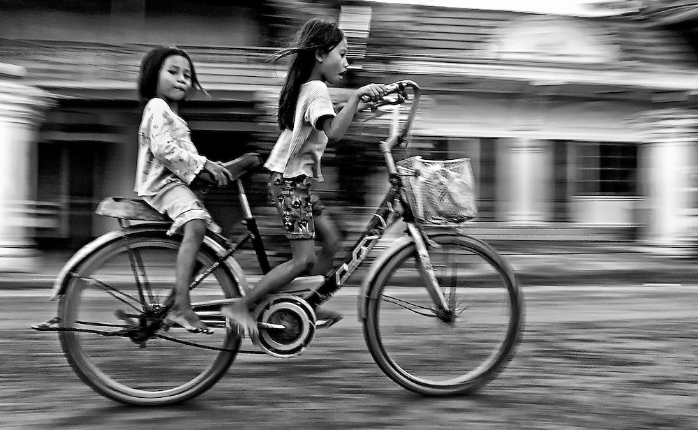 Children cycle through the town of Champasak, Laos.