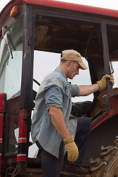farmer getting on a tractor