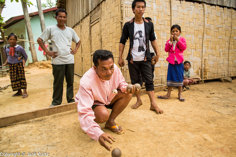 12 MARCH 2013 - ALONG HIGHWAY 13, LAOS:  Men play bocce ball in a village on Highway 13 in rural Laos. Bocce ball was brought to Laos by the French. The paving of Highway 13 from Vientiane to near the Chinese border has changed the way of life in rural Laos. Villagers near Luang Prabang used to have to take unreliable boats that took three hours round trip to get from the homes to the tourist center of Luang Prabang, now they take a 40 minute round trip bus ride. North of Luang Prabang, paving the highway has been an opportunity for China to use Laos as a transshipping point. Chinese merchandise now goes through Laos to Thailand where it's put on Thai trains and taken to the deep water port east of Bangkok. The Chinese have also expanded their economic empire into Laos. Chinese hotels and businesses are common in northern Laos and in some cities, like Oudomxay, are now up to 40% percent. As the roads are paved, more people move away from their traditional homes in the mountains of Laos and crowd the side of the road living off tourists' and truck drivers.    PHOTO BY JACK KURTZ