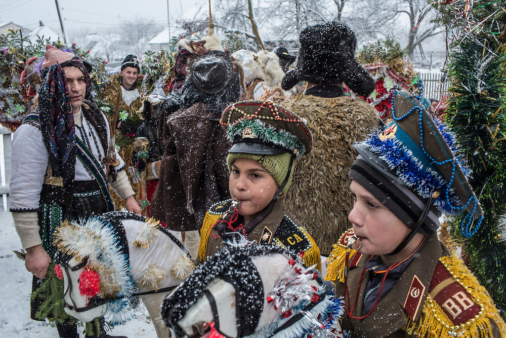 Petrya Velia, 11, center, and Todor Mytyk, 10, right, celebrate the Malanka Festival on Thursday, January 14, 2016 in Krasnoilsk, Ukraine. The annual celebrations, which consist of costumed villagers going in a group from house to house singing, playing music, and performing skits, began the previous sundown, went all night, and will last until evening.