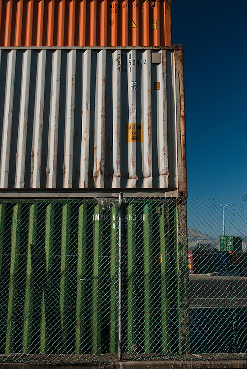 Metal frieght containers stacked at the cargo terminal in Lyttelton Port of Christchurch, surrounded by chainlink fence