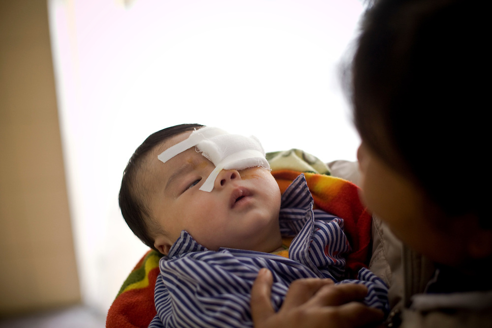 Patients in the childrens ward in Hanoi. Three month old Vinh Phuc and mother To Thi Sang 19.