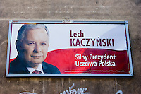 "bill board poster for lech kaczynski showing his face and red and white background in krakow poland. the writing reads ""lech kaczynski - silny prezydent uczciwa polska"""
